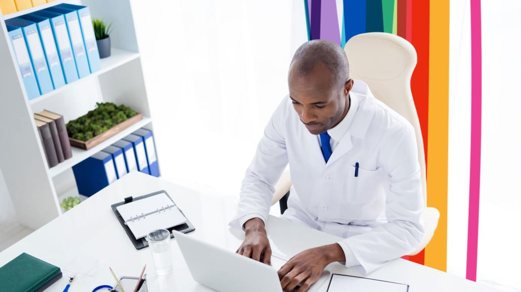 An image of a physician working in his office on his laptop